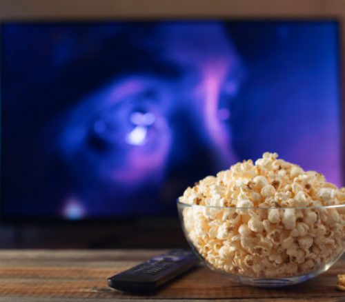 A glass bowl of popcorn and remote control in the background the TV works. Evening cozy watching a movie or TV series at home.